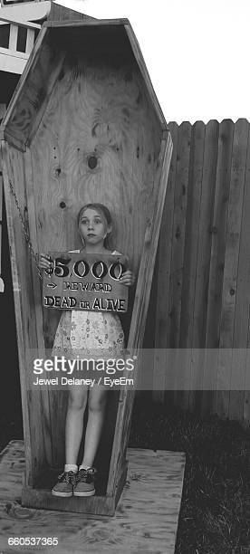 Full Length Of Girl Standing In Coffin While Holding Wanted Poster In Back Yard