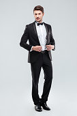 Full length of handsome young man in tuxedo with bowtie standing