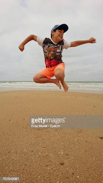 Full Length Of Happy Boy Jumping At Beach Against Sky
