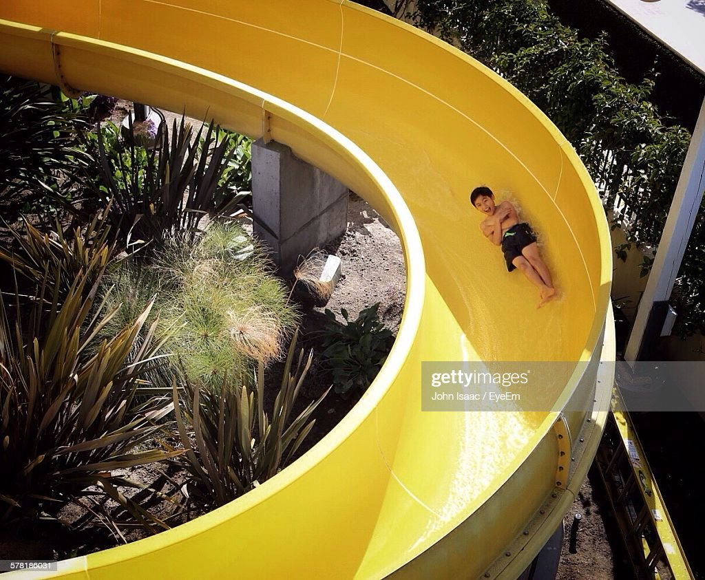Full Length Of Happy Boy On Yellow Water Slide : Stock Photo