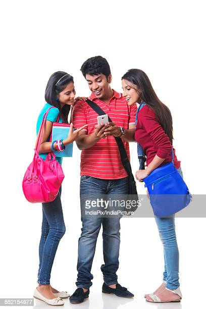 Full length of happy college students using mobile phone against white background