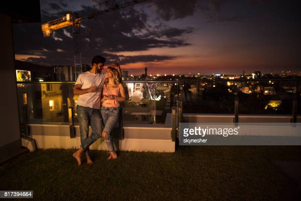 Full length of happy couple falling in love on a terrace by night.