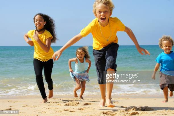 Full Length Of Happy Family Enjoying At Beach