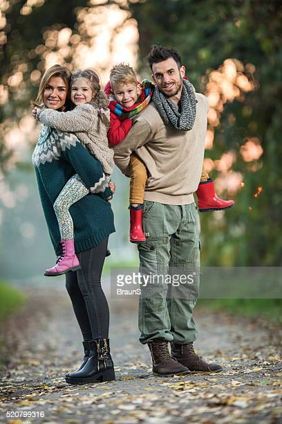 Full length of happy family piggybacking in the park.