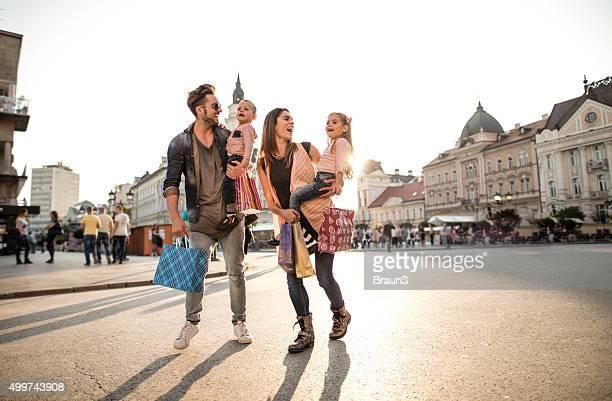 Gesamte Länge der glückliche Familie einkaufen in der Stadt.