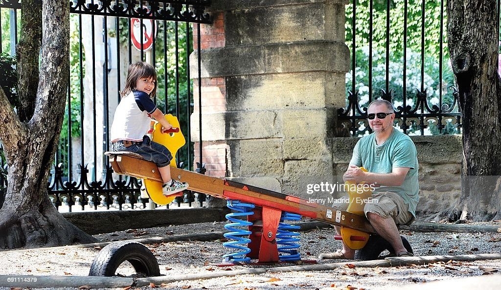 full playground full length of happy father and son on seesaw at playground stock