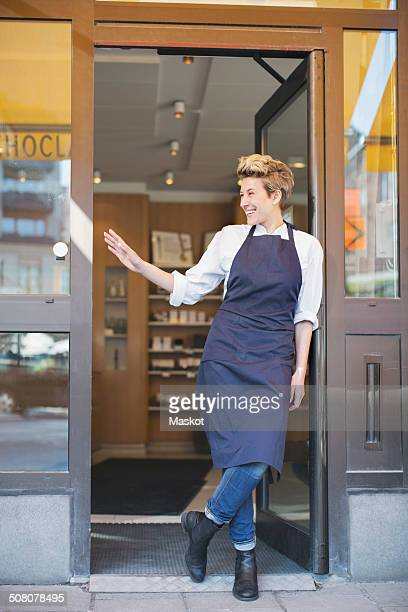 Full length of happy female owner gesturing while standing at cafe entrance