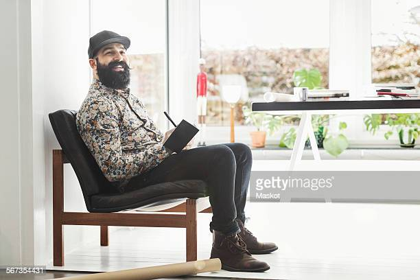 Full length of happy male architect sitting at home office