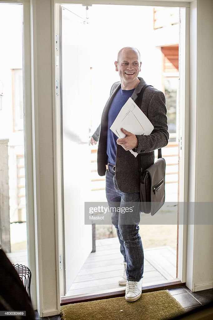 Full length of happy man returning home from office