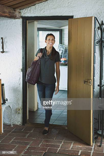 Full length of happy woman entering a house