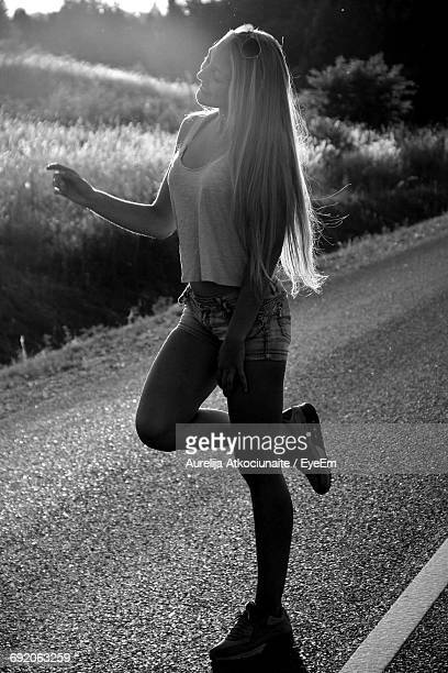 Full Length Of Happy Woman Gesturing While Standing On Road