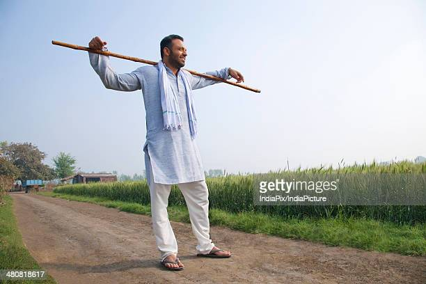 Full length of Indian farmer with stick on shoulders at farm