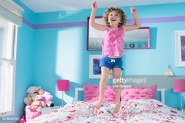 Full length of little girl jumping on bed at home