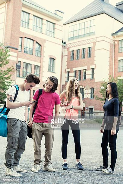 Full length of male and female students standing on high school schoolyard
