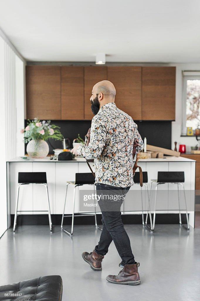 Full length of male art director walking in kitchen
