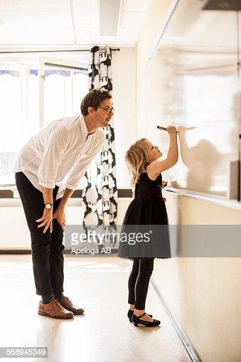 Full length of male teacher watching girl writing on whiteboard
