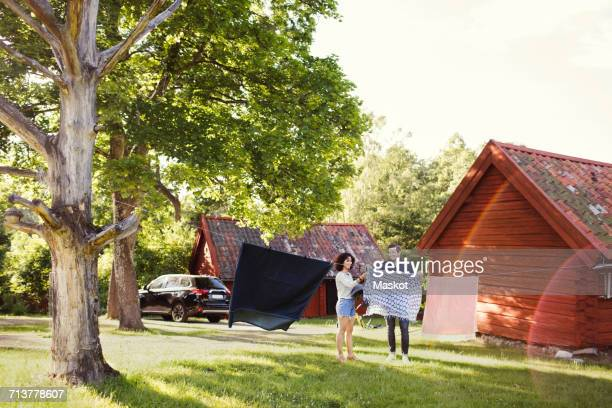 Full length of man and woman drying clothes in backyard on sunny day