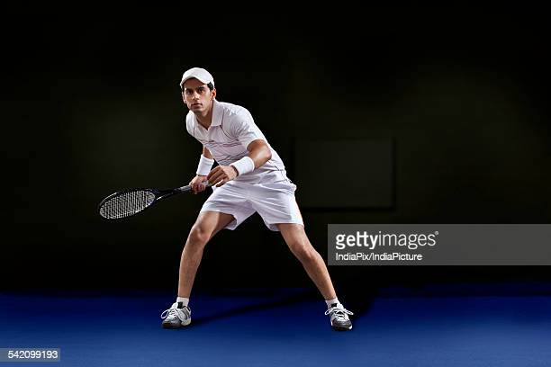 Full length of man in sportswear playing tennis at court