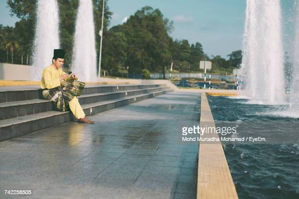 Full Length Of Man In Traditional Clothing Using Phone On Steps By Fountain