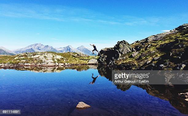 Full Length Of Man Jumping On Lake At Mountain Against Blue Sky