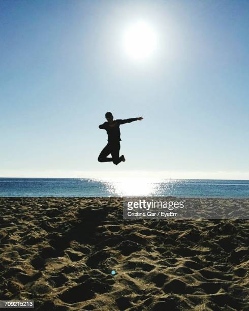Full Length Of Man Jumping Over Beach Against Clear Sky During Sunny Day