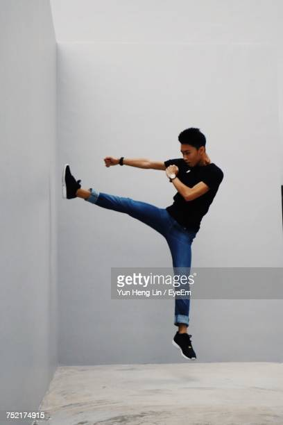 Full Length Of Man Kicking While Jumping Against Wall