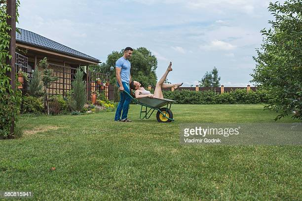 Full length of man pushing girlfriend in wheelbarrow at backyard