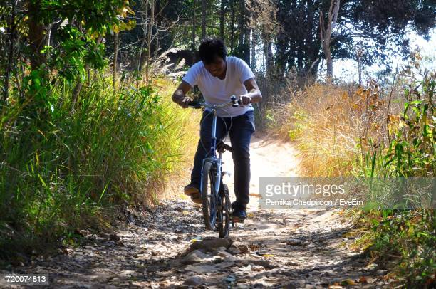 Full Length Of Man Riding Bicycle On Walkway Amidst Plants