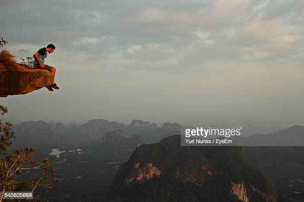 Full Length Of Man Sitting At The Edge Of Mountain Against Sky During Sunset
