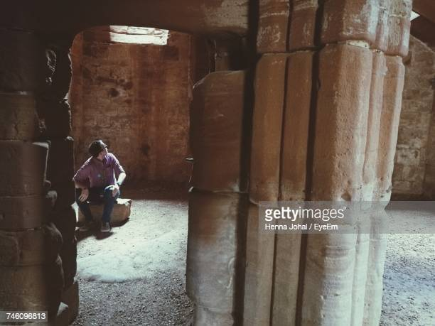 Full Length Of Man Sitting In Ancient Cave