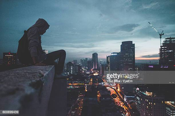 Full Length Of Man Sitting On Building Terrace By Illuminated Cityscape Against Sky During Sunset