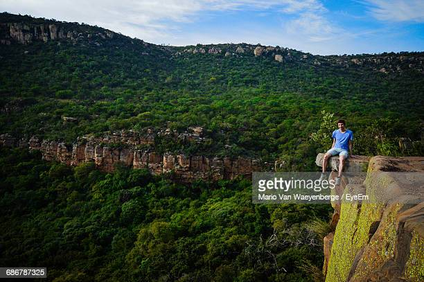 Full Length Of Man Sitting On Cliff Against Green Mountains