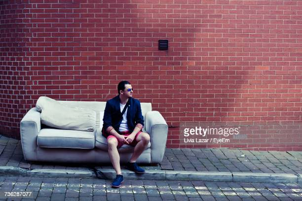 Full Length Of Man Sitting On Sofa Against Brick Wall