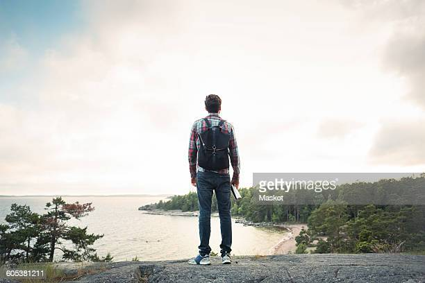 Full length of man standing on rock at lakeshore against cloudy sky