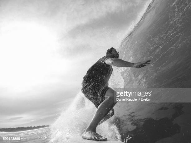 Full Length Of Man Surfing In Sea Against Sky