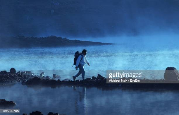 Full Length Of Man Walking At Beach Against Cloudy Sky At Dusk