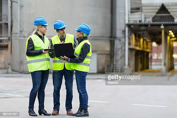 Full length of manual workers using technologies at factory