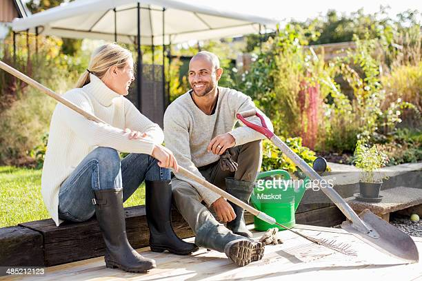 Full length of mature couple with gardening equipment sitting at yard