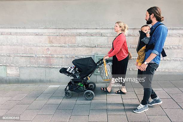 Full length of mid adult parents with baby boy and carriage walking on sidewalk