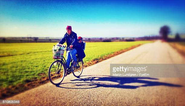 Full length of mother and son riding bicycle on country road