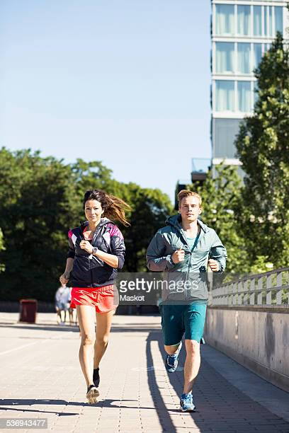 Full length of multi-ethnic couple jogging on bridge