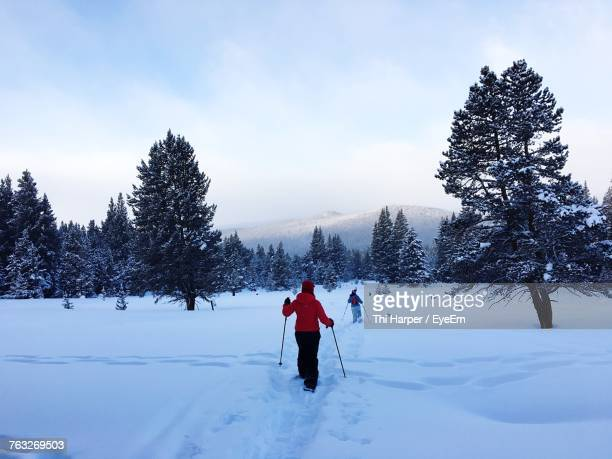 Full Length Of People Hiking On Snow Covered Field Against Sky