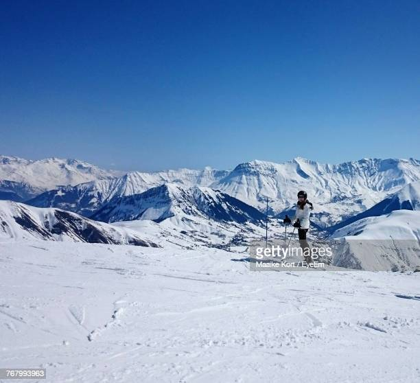 Full Length Of Person Skiing On Snow Covered Field By Mountains Against Clear Blue Sky