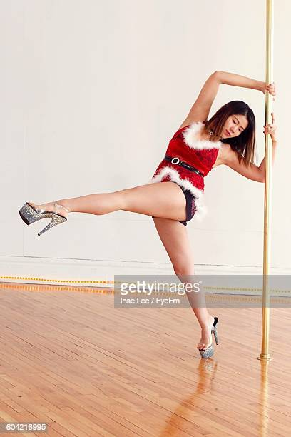 Full Length Of Pole Dancer Dancing Against Wall