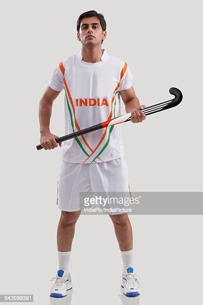 Full length of portrait of confident young man holding hockey stick isolated over gray background