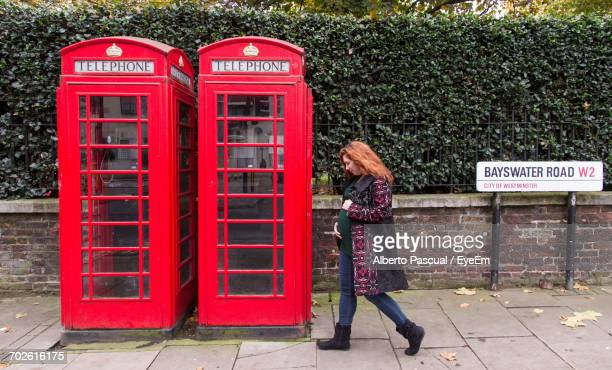 Full Length Of Pregnant Woman Walking By Telephone Booths At Bayswater Road
