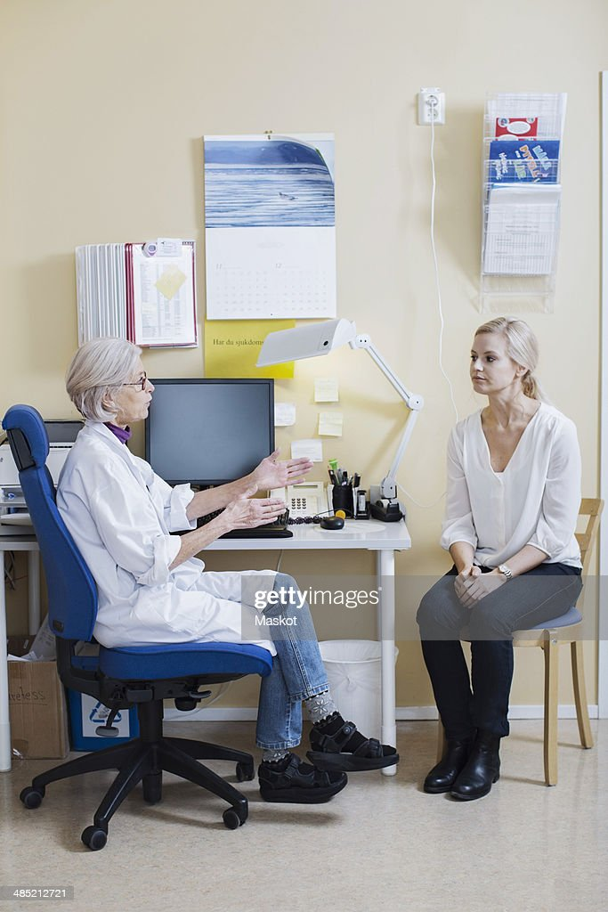 Full length of senior female doctor talking with woman in clinic