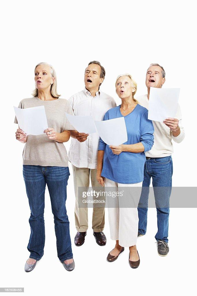 Full length of senior people singing together against white