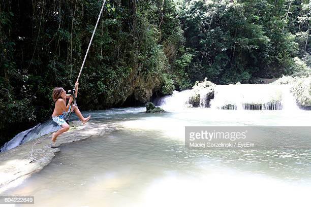 Full Length Of Shirtless Boy Swinging On Rope Over River At Forest