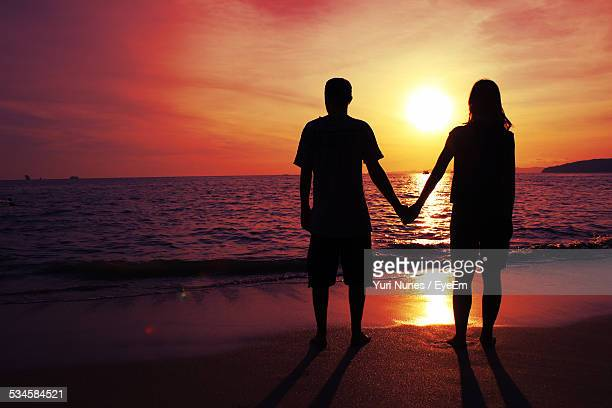 Full Length Of Silhouette Couple Standing On Beach Against Orange Sky